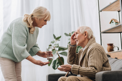 forgetful old man being helped by woman to take his medication