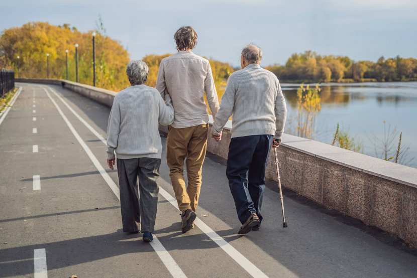 old couple walking down bridge with young man
