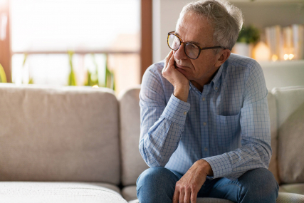 older man sitting on couch in a depressive state