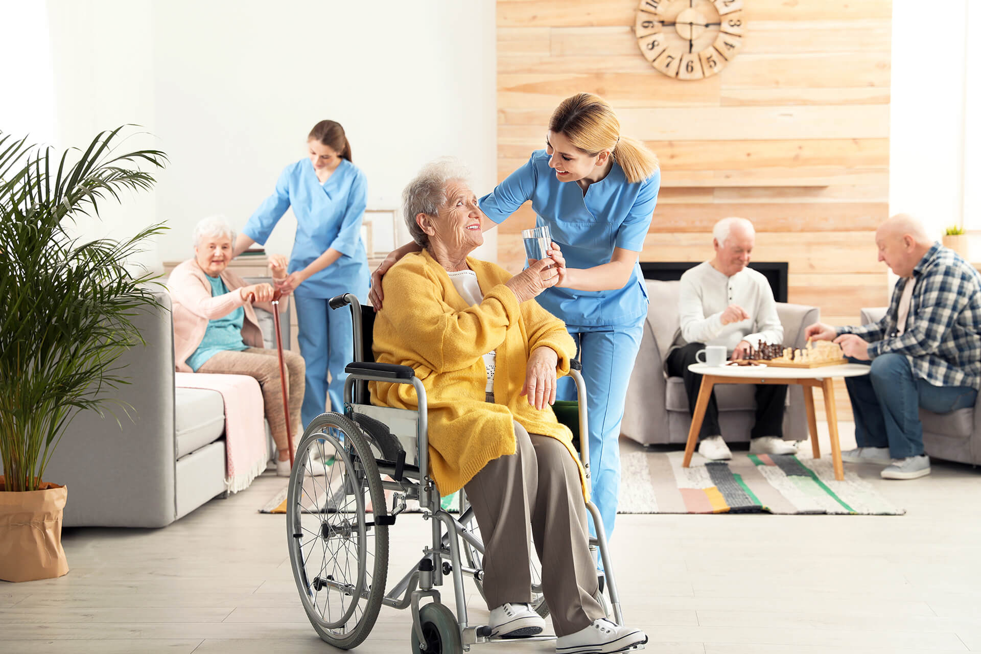 old woman in wheelchair receives medication from nurse